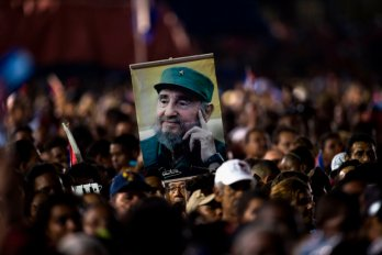 A photograph of a crowd holding up a picture of Fidel Castro.