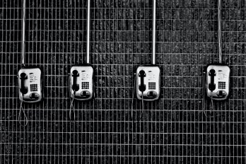 A black and white photo of a row of four empty phones mounted on a chain-link fence.