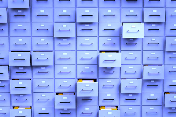 A wall of filing cabinets with some drawers open.