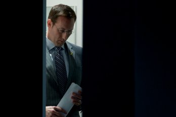 A photo of Peter MacKay framed by a partially open door. He is looking downward and carrying a sheaf of papers in his hand.