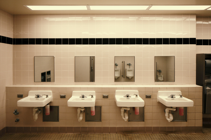 Photograph of a public men's restroom with sinks and mirrors against a wall. Urinals can be seen in the reflection of the mirrors.