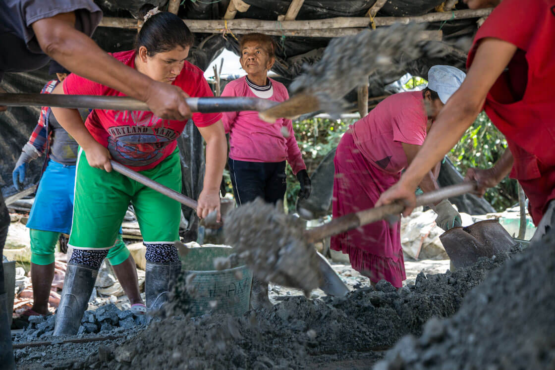 A group of women sift through buckets of mining ore with shovels.