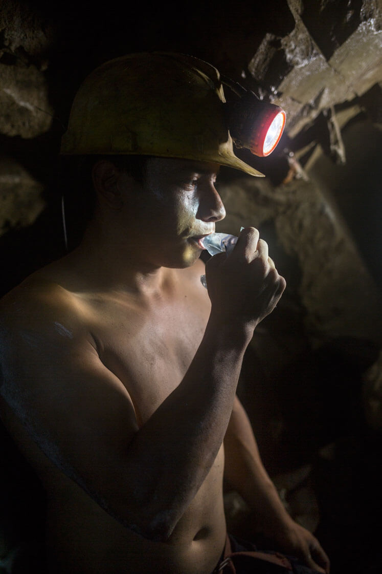 A miner wearing a hard hat and standing in a dark cave drinks water from a small plastic bag.