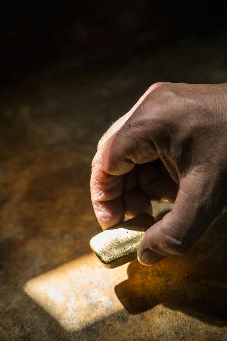 Closeup of a hand holding a rectangular gold bar.