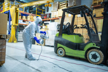 A shielded worker cleans in an empty warehouse