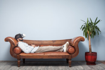 A man with a VR headset reclines on a couch