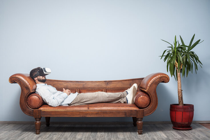 A photo of a bearded man wearing a VR headset reclining on a leather couch next to a potted plant.