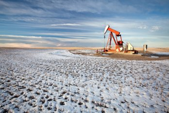 An oil pumpjack stands in an open prairie field covered with snow.