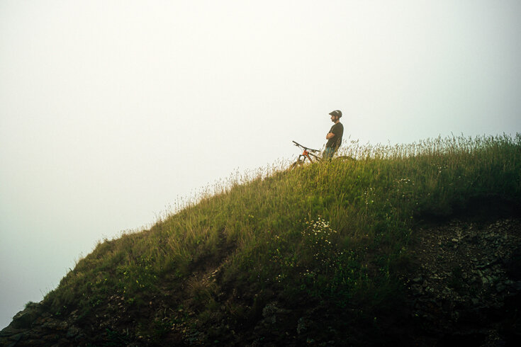 A cyclist looks out on a cliff