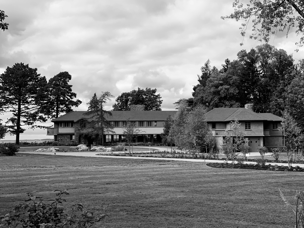 A black and white photo of a Frank Lloyd Wright home surrounded by trees.