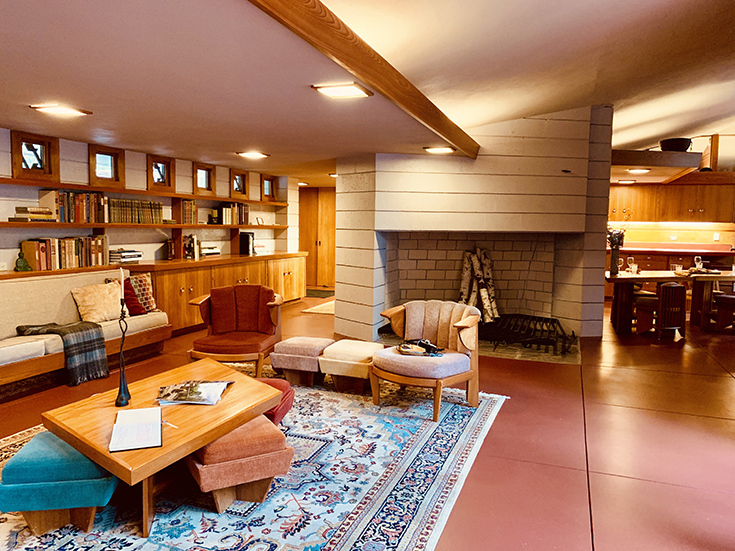 A photo of a living room in a Frank Lloyd Wright house, with slanted ceiling and a lot of wood. There are armchairs, a fireplace, and bookshelves on the walls.