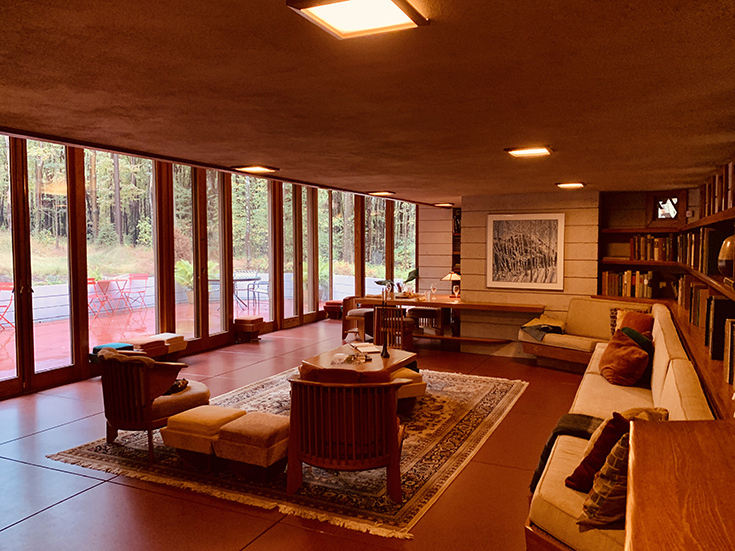 A photo of a living room in a Frank Lloyd Wright house. It's the same living room as the previous photo, but this one shoes the wall of windows, which look out onto trees and a sitting area.