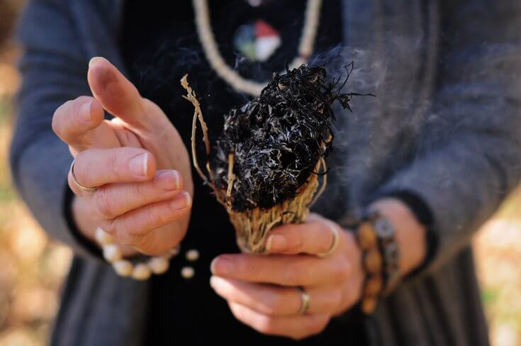 Closeup of a woman's hands holding sage for smudging.