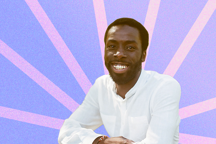 A photograph of the writer, Desmond Cole, with his arms crossed and smiling at the camera. The background is purple with pink stripes.