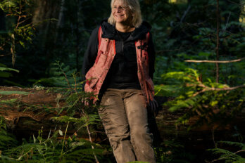 A photo of a smiling woman standing in a forest, leaning on a log.