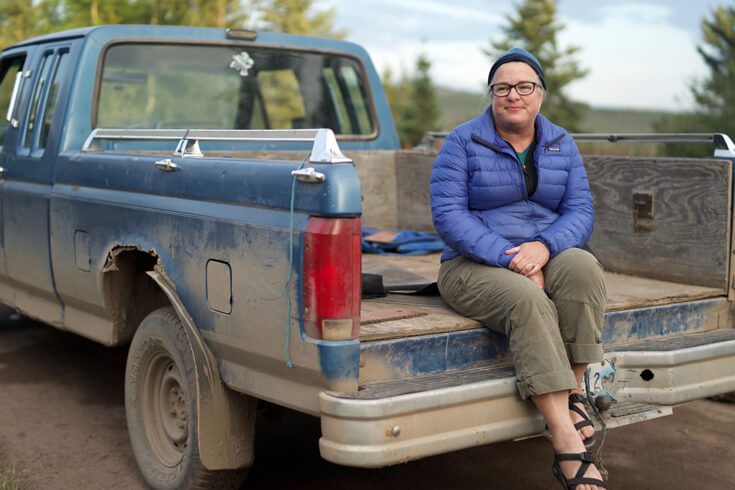 A woman in a blue jacket sits on the edge of the bed of a blue pickup truck.