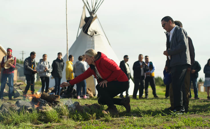 A woman kneels in front of a fire and holds out an offering of tobacco. She is surrounded by a loose crowd of people.