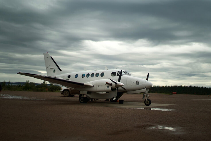 A small propeller plane waits for passengers on the gravel of an airstrip.