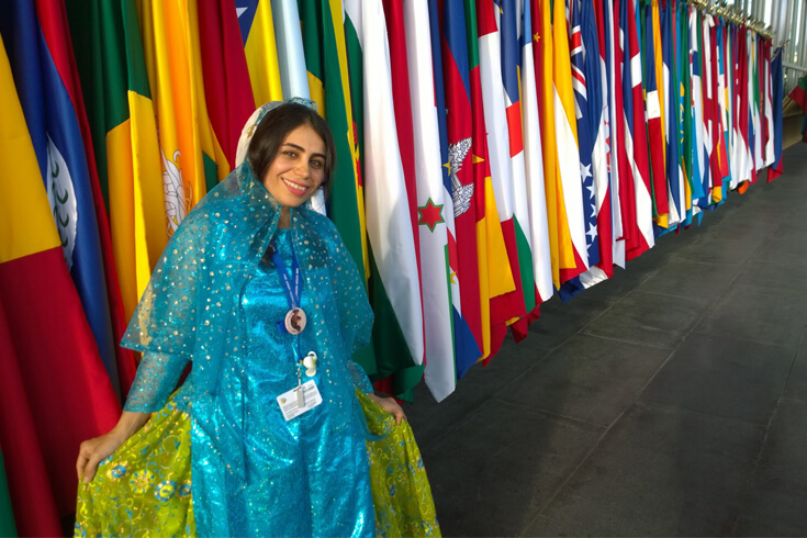 Ghanimat Azhdari, a young woman in a blue dress, poses and smiles against a backdrop of nations' flags.