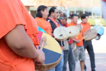 A photo of people in a row wearing orange t-shirts and drumming and singing.