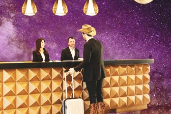 Illustration of a man in a suit, cowboy hat, and cowboy boots standing at a gold-plated counter and pulling a suitcase. The background is celestial purple. In the distance, a large moon hangs in the sky.