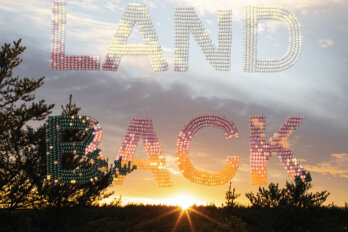A photo of a sunrise or a sunset with a slightly darkened sky and shells spelling out the words land back.