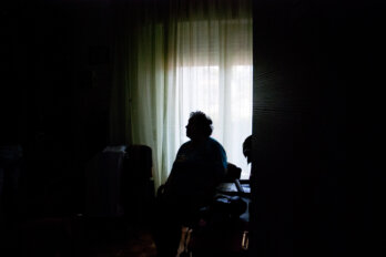 Senior woman sits alone in a dark room, seen through a doorway. She is in shadow, backlit by a window.