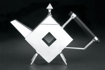 A black and white photo of a geometric metal teapot, which has a body shaped like a diamond.