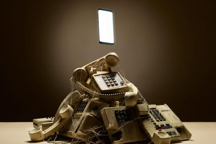 A pile of old telephones covered in cobwebs, with a smartphone floating overtop.