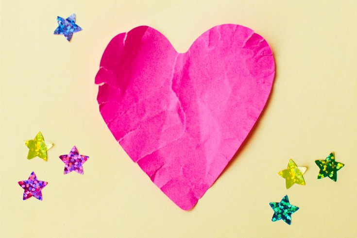 Pink paper heart curling slightly against a yellow background, with several sparkly star stickers around it.