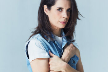 Portrait of comedian Meredith MacNeill, in a sparse room. MacNeill looks directly at the camera, hugging the sleeves of her denim vest.