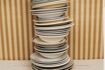 stack of plates in front of a yellow wall
