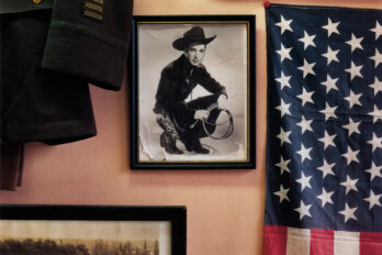 A photo hangs on the wall of a man with a cowboy hat and boots, holding a whip. On the wall also hangs an American flag, and what appears to be a military jacket.