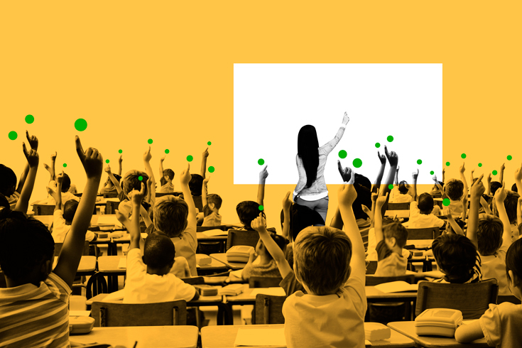 Photo of a teacher standing at the front of a classroom, raising her hand to a whiteboard. Behind her, a class full of students raises their pointer fingers. Above each finger is an illustration of a green dot, like an unanswered notification.
