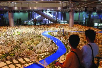 Two people look out at a room-sized model in the Shanghai Urban Planning Museum shows what central Shanghai will look like in 2020.