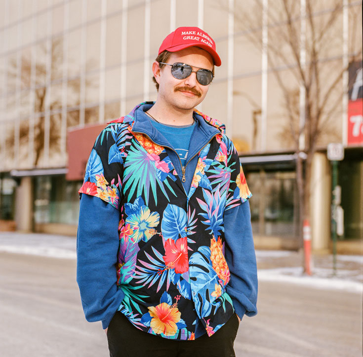 """A young mustachioed man wearing aviator sunglasses, a Hawaiian shirt over a blue sweatshirt, and a red hat that reads """"Make Alberta Great Again"""" smiles at the camera."""
