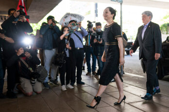 A photograph of Meng Wanzou, wearing a dark dress and heels, being led past a crowd of people photographing her.