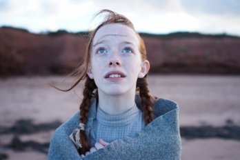 Screenshot of the actress who plays Anne Shirley on the TV show Anne with an E. She has red hair and freckles and is looking towards the top of the frame while wrapped in a grey blanket.