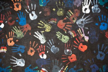 Photograph of children's handprints in multicoloured paint on a textured black wall.