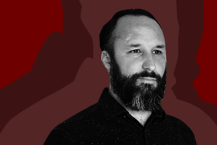 A photo of the poet looking beyond the camera. He is wearing a dark shirt and has a dark beard. The photo is black and white and the background is three shades of burgundy.