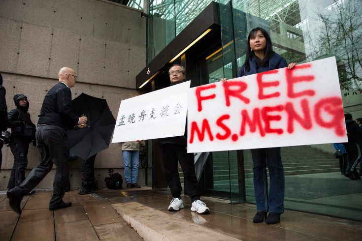 """Two people hold signs outside a courthouse. One reads """"Free Ms. Meng."""""""