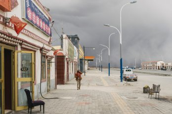 A photo of a deserted street in Madoi County against a grey sky.