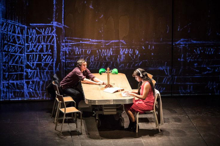Two people sit at a library desk on stage.