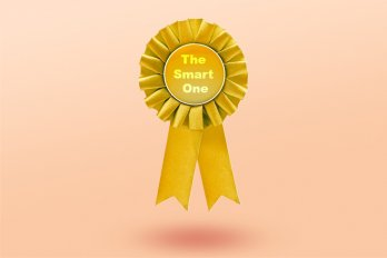"A gold award ribbon that says ""The Smart One,"" floating against a pale pink background."