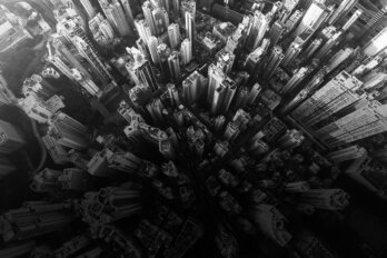 Black and white photo of a skyscraper filled city from directly above.