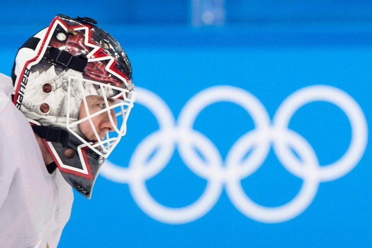 Photograph of a Hockey Player in front of the Olympic Logo