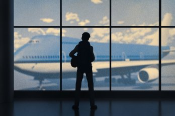 Silhouette of a person standing at a window through which you can see a passenger airplane.