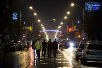 Toronto police officers work on Danforth Avenue at the scene of the shooting in Toronto on July 23.