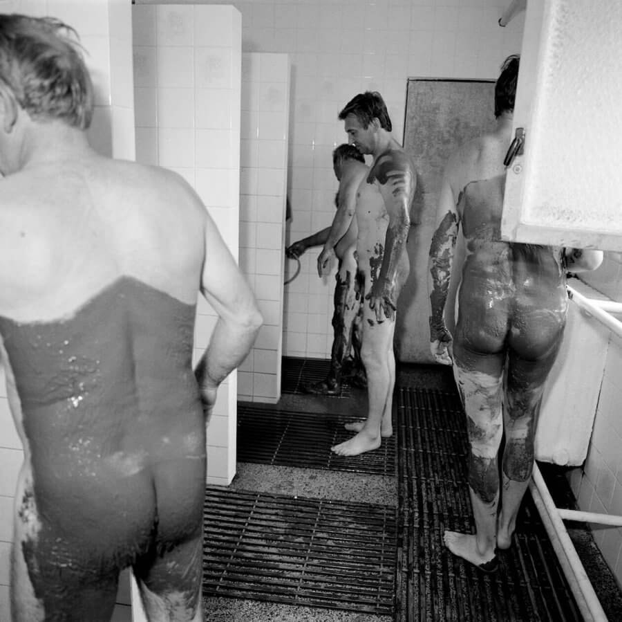 Men and women, covered partially in mud, waiting for shower