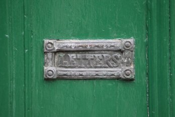 old mailbox on a green door